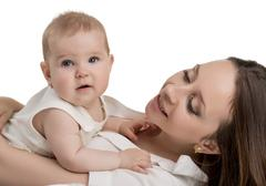 Happy young mother tenderly holding her daughter - stock photo