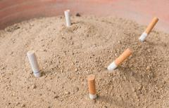 Cigarette Butts and Ash in Public Terracotta Ashtray Big Tray. - stock photo
