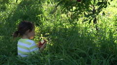 Adorable toddler under munches apple under tree - stock footage