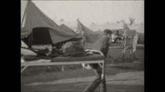 CCC carry beds past tents CU 1936 Stock Footage