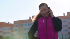 Attractive Caucasian woman dressed in sport clothes talking on cellphone in sun Stock Footage