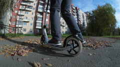 Woman riding the kick scooter on the asphalt road with fallen leaf in city park Stock Footage