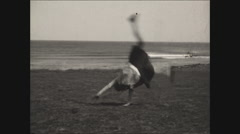 Girl does cartwheels at seaside 1930 Stock Footage