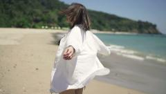 Young, happy woman turning around on beach Stock Footage