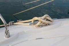 Stock Photo of Close-up nautical knot rope tied around stake on boat or ship, boat mooring r