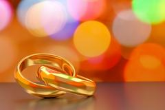 couple of gold wedding rings on bokeh background - stock illustration