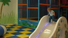 Pretty boy playing on toy hill at playground Stock Footage