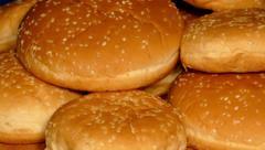 4k – Many hamburger buns on wooden board Stock Footage