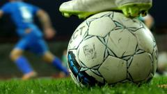 Cleats on ball next to football field,close up,part of soccer game in background - stock footage