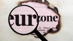 Magnifying glass on eurozone paper hole Stock Footage