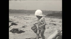 Toddler on beach with bucket - stock footage