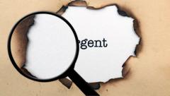 Magnifying glass on urgent text - stock footage
