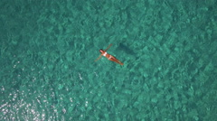 Stock Video Footage of Aerial - Young woman floating in crystal clear water