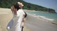 Young, happy woman stretching arms on beach, slow motion 240fps Stock Footage