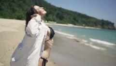 Young, happy woman stretching arms on beach Stock Footage