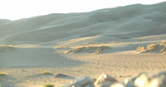 4K moving shot footprints on sand dunes field with rocks and brush at sunset Stock Footage