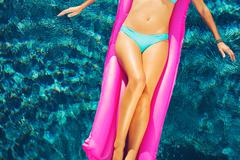 Woman Relaxing Floating on Raft in Pool - stock photo