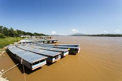 Row of Laos and Chinese cargo boats anchored in Mekong river - stock photo