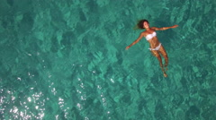 Aerial - Beautiful young woman floating on water surface in crystal clear ocean Stock Footage