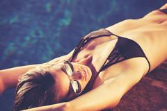 Beautiful Woman in Bikini Relaxing By the Pool at Sunset Stock Photos