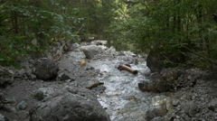 Small river splitting and streaming towards cliff Stock Footage