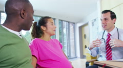 4K Friendly doctor talking to couple who are expecting a baby  - stock footage