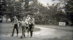 1949: Baby's first horse ride with dad holding for safety. Stock Footage