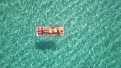 Aerial - Rotating above woman on pool raft in crystal clear water, closeup Stock Footage
