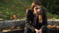 Man long hair sitting on bench in autumn park 4K Stock Footage
