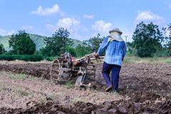 Thai farmer using walking tractors for cultivated soil for prepare plantation - stock photo