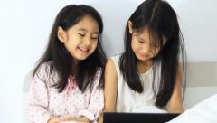 Little Asian girls play on tablet on the bed together, Zoom out shot Stock Footage