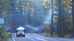 A truck tows an airstream trailer down a foggy forest road. Stock Footage