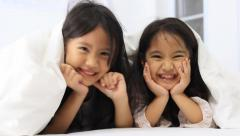 Little Asian girls play hide and seek in the blanket on the bed, Zoom out shot Stock Footage