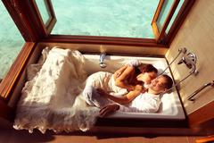 Bride and groom laying down in a bathtub in water villa near Maldives - stock photo