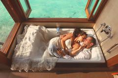 Bride and groom laying down in a bathtub in water villa near Maldives Stock Photos