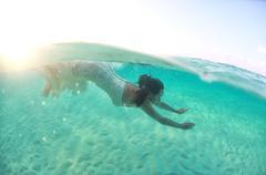 Beautiful young women in dress diving in ocean near Maldives islands Stock Photos