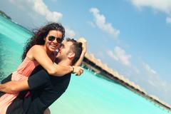 Beautiful couple on their honeymoon in tropical island of Maldives - stock photo