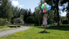 Young woman in dress with many colorful balloons walking in the green park Stock Footage
