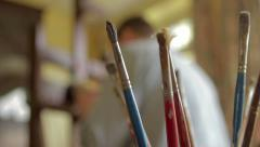 Brushes in artists's studio with soft focus artist in background Stock Footage