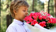 Young boy with beautiful bouquet of red roses. Stock Footage