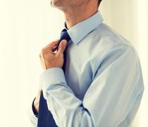 close up of man in shirt adjusting tie on neck - stock photo
