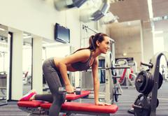 Happy woman with dumbbell flexing muscles in gym Stock Photos