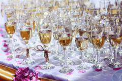Many glasses filled with champagne at wedding reception - stock photo