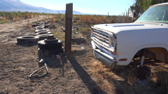 Old abandoned pickup truck int he desert and tires strewn about. Stock Footage