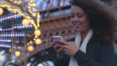 Girl writes SMS on the phone next to the carousel near Eiffel Tower in Paris in Stock Footage