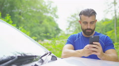 4K Young man in fitness clothing looking at mobile phone beside his car Stock Footage