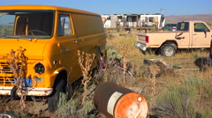 An abandoned mobile home in the desert is surrounded by old trucks and cars and Stock Footage