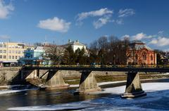 Stock Photo of People crossing old pedestrian bridge over Uzh river,Uzhgorod,Ukraine