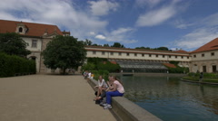 Tourists sitting near the small lake from Wallenstein Garden, Prague Stock Footage