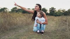 mother and daughter watching at the sky on the autumn field - stock footage
